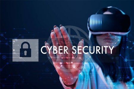 Foto de Selective focus of young woman in virtual reality headset pointing with hand at cyber security illustration on dark background - Imagen libre de derechos