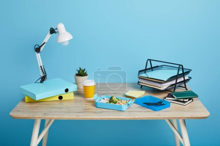 Photo for Studio shot of workspace with table and lunch box on blue background - Royalty Free Image