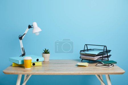 workplace with papers, succulent and coffee in plastic cup on wooden table on blue background