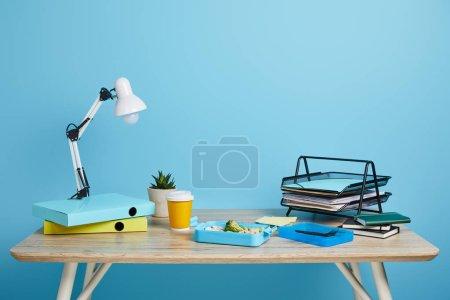 Photo pour Espace de travail avec boîte à lunch et café pour aller sur table en bois sur fond bleu - image libre de droit