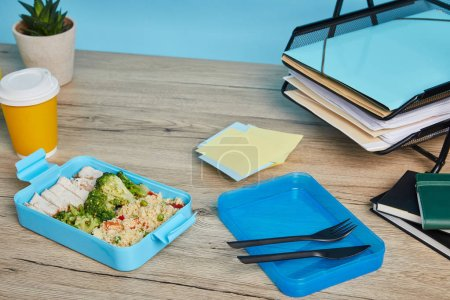 Photo for Plastic lunch box with tasty and healthy food at workplace with papers on wooden table on blue background - Royalty Free Image