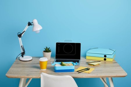 Photo for Workplace with laptop and lunch box on wooden table on blue background, illustrative editorial - Royalty Free Image