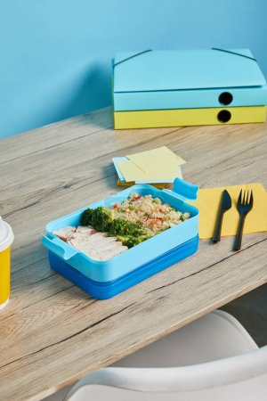 Photo for Lunch box full of delicious rice with broccoli and chicken on wooden table on blue background - Royalty Free Image