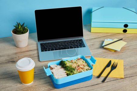 Photo for Lunch box with rice, chicken and broccoli at workplace with laptop on wooden table on blue background, illustrative editorial - Royalty Free Image