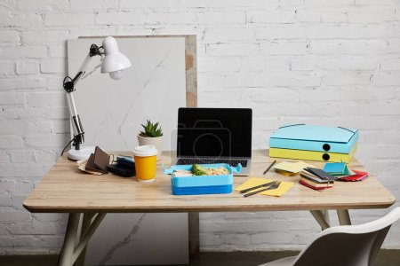 Photo for Lunch box with delicious food at workplace with laptop and papers on wooden table on white background, illustrative editorial - Royalty Free Image