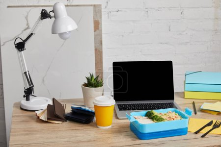 Photo for Blue plastic lunch box with healthy food on wooden table with laptop and succulent on white background, illustrative editorial - Royalty Free Image