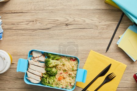 Top view of plastic lunch box with rice, broccoli and chicken on wooden table