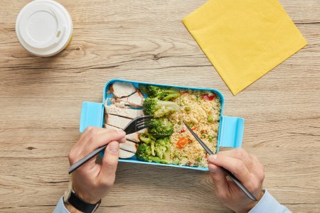 Cropped view of man eating healthy lunch with risotto, broccoli and chicken at wooden table