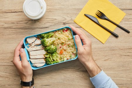 Photo for Cropped view of man sitting at table and holding lunch box with healthy and tasty food - Royalty Free Image