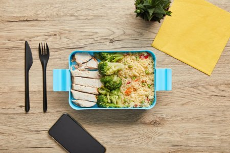 Photo for Top view of healthy nutritious risotto, vegetables and chicken in plastic lunch box on wooden table - Royalty Free Image