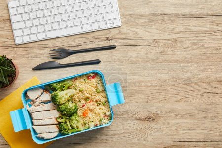 Photo for Top view of lunch box with rice, broccoli and chicken near computer keyboard on wooden table - Royalty Free Image