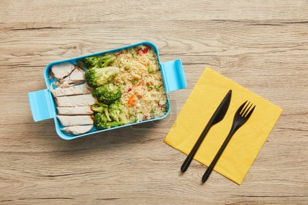 Top view of plastic lunch box with risotto, chicken and broccoli on wooden table
