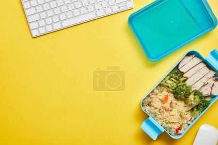 Photo pour Vue supérieure de la nourriture délicieuse saine dans la boîte de déjeuner en plastique et le clavier d'ordinateur sur le fond jaune - image libre de droit