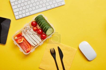 Photo for Top view of lunch box with vegetables and chicken on yellow background with computer keyboard - Royalty Free Image