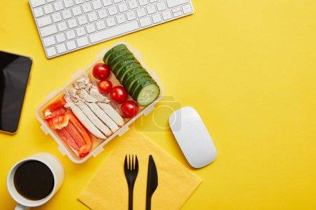 Photo pour Vue supérieure de boîte de déjeuner avec le repas sain et la tasse de café au lieu de travail sur le fond jaune - image libre de droit