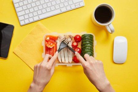 Foto de Vista recortada de la mujer comiendo almuerzo saludable y sabroso en el lugar de trabajo sobre fondo amarillo - Imagen libre de derechos