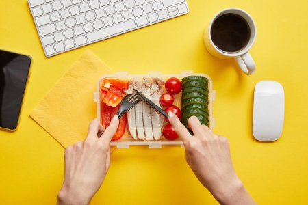 Photo for Partial view of woman eating delicious chicken and fresh vegetables at workplace on yellow background - Royalty Free Image