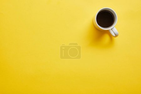Photo for Top view of cup of hot delicious coffee on yellow background - Royalty Free Image