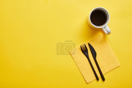 Photo for Top view of cup of hot delicious coffee and disposable fork and knife with yellow napkin on yellow background - Royalty Free Image