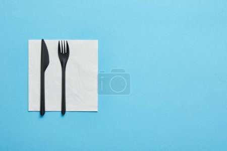 Photo for Top view of disposable fork and knife lying on napkin on blue background - Royalty Free Image