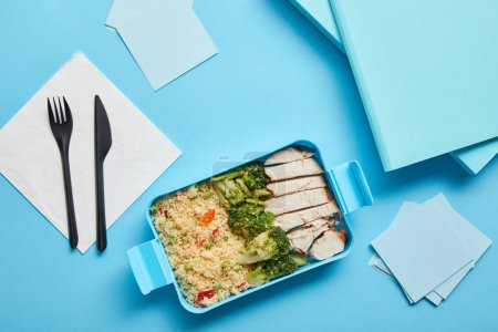 Foto de Vista superior de la lonchera con sabroso risotto nutritivo, pollo y brócoli en el lugar de trabajo sobre fondo azul - Imagen libre de derechos
