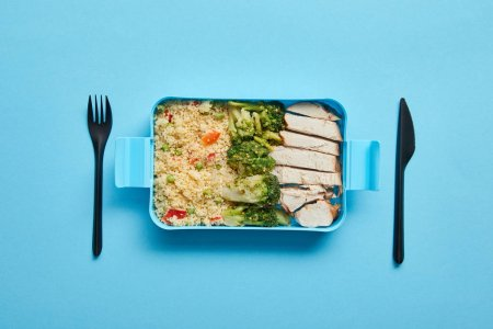 Top view of lunch box with risotto, broccoli and chicken with disposable fork and knife on blue background