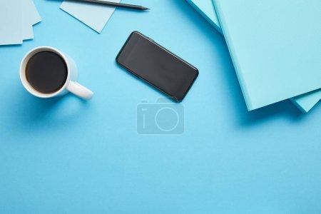 Photo pour Vue supérieure du smartphone avec l'écran blanc et la tasse de café au lieu de travail sur le fond bleu - image libre de droit