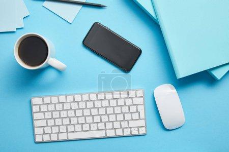 Photo pour Vue supérieure du lieu de travail avec la tasse de café, les dispositifs numériques et les papiers sur le fond bleu - image libre de droit