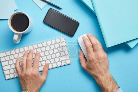 Photo pour Vue recadrée de l'homme en utilisant un clavier d'ordinateur et une souris d'ordinateur sur le lieu de travail avec des papiers, un smartphone et une tasse de café sur fond bleu - image libre de droit