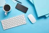 """Постер, картина, фотообои """"Top view of workspace with digital devices, papers and cup of coffee on blue background"""""""