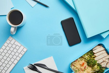 Photo for Top view of workplace with digital devices, papers and lunch box with healthy and tasty food on blue background - Royalty Free Image
