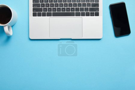 Top view of laptop keyboard, computer mouse, smartphone and cup of coffee on blue background, illustrative editorial