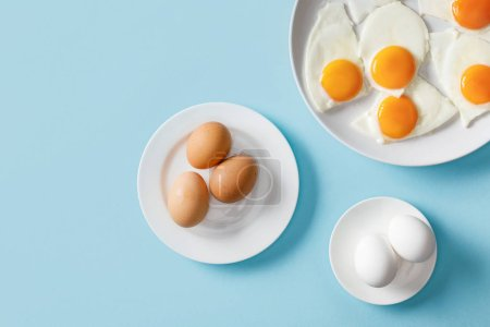 Photo pour Top view of fresh boiled and fried eggs on white plates on blue background - image libre de droit