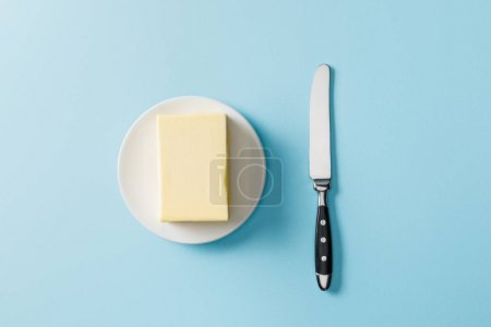Photo for Top view of butter on white plate and knife on blue background - Royalty Free Image
