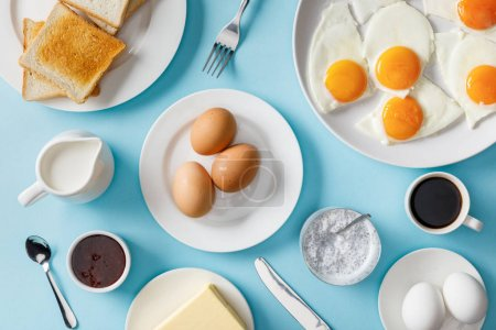 Photo for Top view of served breakfast with boiled and fried eggs on blue background - Royalty Free Image
