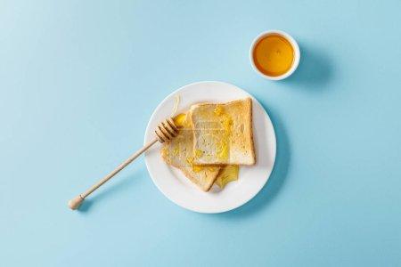 Photo pour Vue supérieure des toasts avec le miel et l'oursssuron en bois sur la plaque blanche sur le fond bleu - image libre de droit