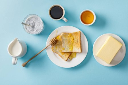 Photo for Top view of coffee, milk, yogurt with chia seeds, butter, honey, toasts with honey and wooden dipper on white plates on blue background - Royalty Free Image