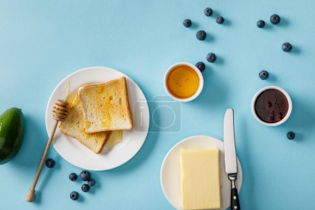 Photo for Top view of avocado, butter, honey, jam, scattered blueberries and two toasts on white plates on blue background - Royalty Free Image