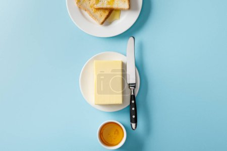 Photo for Top view of butter, knife, toasts on white plates and bowl with honey on blue background - Royalty Free Image