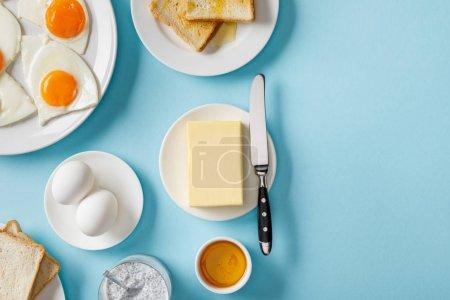Photo pour Vue supérieure du beurre, des toasts, des oeufs frais et frits sur des plats blancs, du yaourt avec des graines de et du bol avec du miel sur le fond bleu - image libre de droit