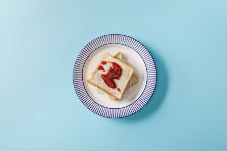 Photo for Top view of toasts with jam on plate on blue background - Royalty Free Image