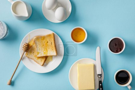 Photo for Top view of served breakfast with yogurt, milk, coffee, jam, honey, butter and knife, toasts on white plates on blue background - Royalty Free Image