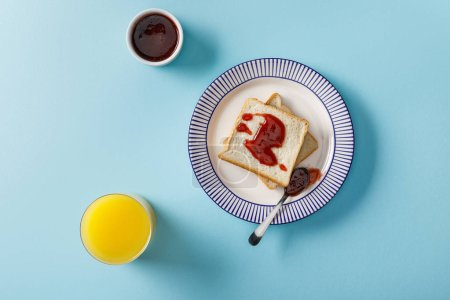 Photo pour Top view of orange juice, toasts, bowl and spoon with jam on plate on blue background - image libre de droit
