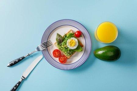 Photo pour Vue supérieure de pain grillé avec le guacamole, l'avocat et le jus d'orange sur le fond bleu - image libre de droit