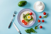 "Постер, картина, фотообои ""top view of toast with guacamole, avocado, boiled eggs, scattered cherry tomatoes and spinach on blue background"""