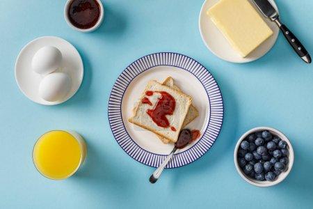 Draufsicht auf Toasts mit Marmelade, Orangensaft, gekochten Eiern, Butter und Blaubeeren auf blauem Hintergrund