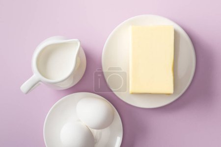Photo for Top view of butter, milk jug and boiled eggs on white plates on violet background - Royalty Free Image