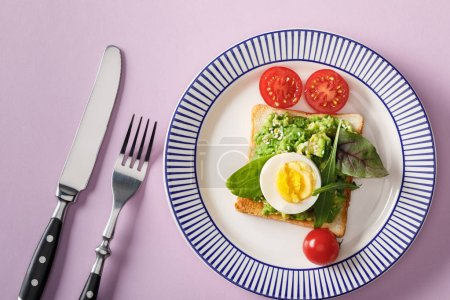 Photo for Top view of toast with guacamole, boiled egg, spinach, cherry tomatoes, fork and knife on ornamental plate on violet background - Royalty Free Image