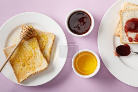 Photo for Top view of toasts with jam and honey, bowls and wooden dipper on violet background - Royalty Free Image