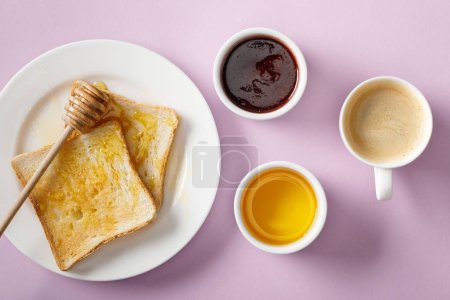 Photo for Top view of bowls, toasts with honey on white plate, wooden dipper, jam and cup of coffee on violet background - Royalty Free Image